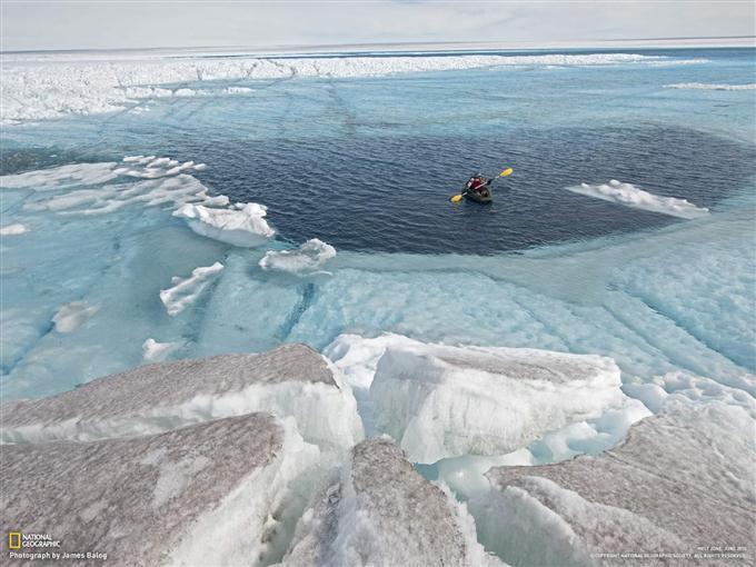 深さ30メートルほどの氷上の湖を進むカヤック(グリーンランド)